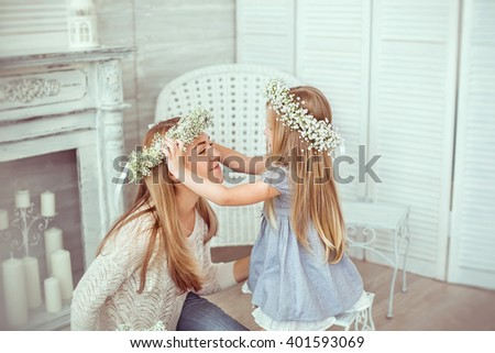 A daughter is putting a floral wreath on her mother. A mother is having jeans and white blouse on. The girl is having a light blues dress. The atmosphere of happiness is all around them. - stock photo