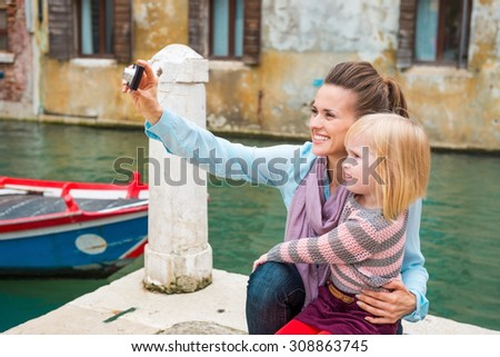A daughter looks on as her mother happily takes a photo of one of the beautiful buildings in Venice. - stock photo
