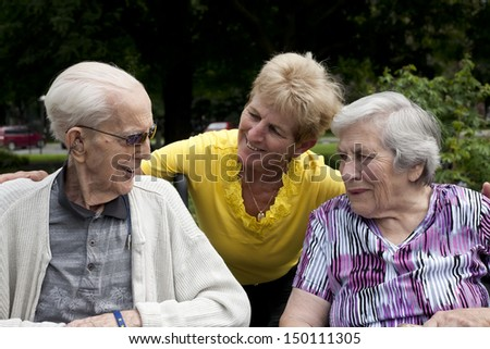 A daughter visiting her senior parents and ejoying their company out doors in a park.