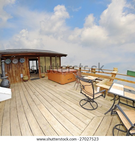 A deck with a hot tub and tables high up with a sky view.  Cabin in the sky, wide angle fisheye view. - stock photo