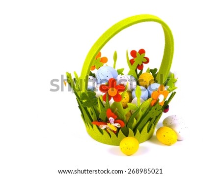 A decorated basket of felt filled with plastic Easter eggs in pastel colors - stock photo