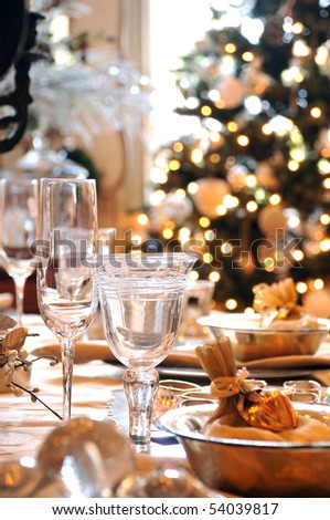 A decorated christmas dining table with wine glasses and christmas tree in background - stock photo