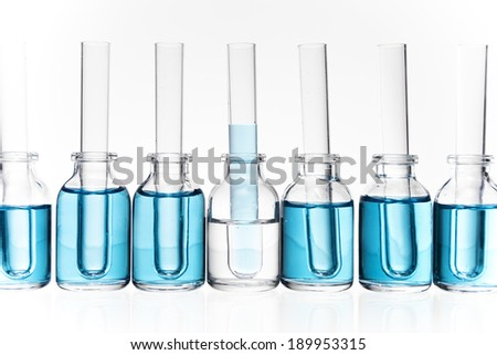 A decorative arrangement of glass science vials and test tubes in a row with blue liquid.