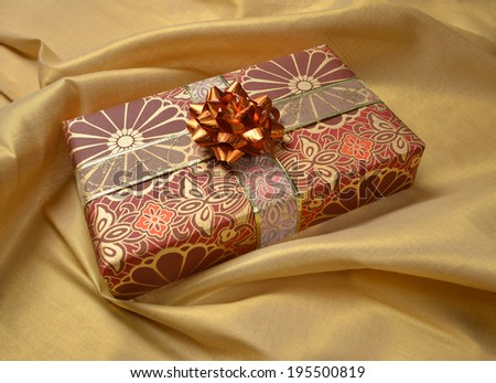 A decorative gift box against a golden drapery background - stock photo