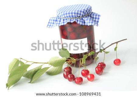 a decorative glass with boiled sour cherries with a twig with leaves and fruits before a bright background - stock photo