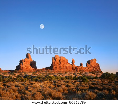 A Deep Blue Afternoon Sky And Daylight Full Moon Rising Over Red Sandstone Rock Forms At Arches National Park, Utah, USA - stock photo