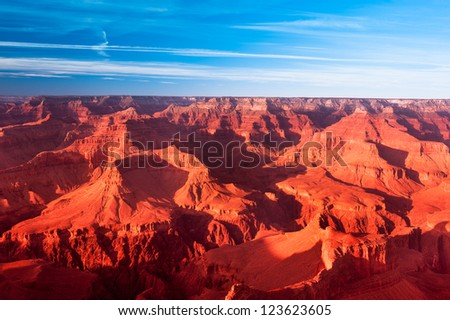 A deep orange sunset at the Grand Canyon turns the mountains a vibrant orange. - stock photo