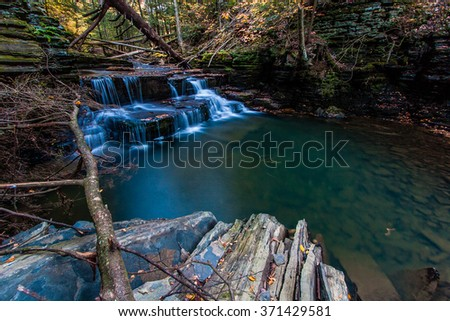 A deep pool formed by a waterfall holds trout - stock photo