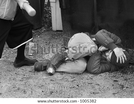A defenseless homeless man being beaten with a bat.  Black and white and film grain effects added for drama. - stock photo