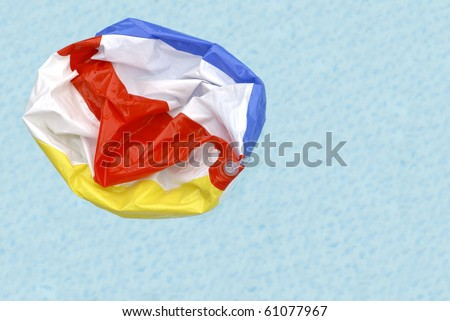 A deflated beach ball floating in a swimming pool symbolizing the end of summer. - stock photo