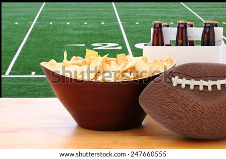 A deflated football and Six Pack of Beer and bowl of chips on a table in front of a big screen TV with a Football field. Great for Super Bowl themed projects. Horizontal format. - stock photo
