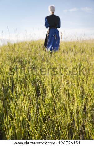 A defocused Amish woman walking in a field of grass - stock photo