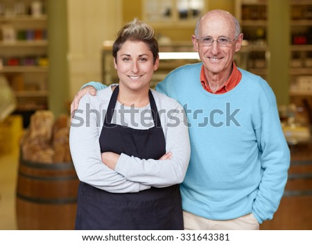 A deli owner and his daughter standing in their shop - stock photo