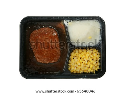 a delicious and nutricous  classic salisbury steak tv dinner with mashed potatoes and corn in its black plastic tray, isolated on white - stock photo