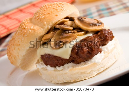 A delicious burger topped with swiss cheese and sauteed mushrooms.