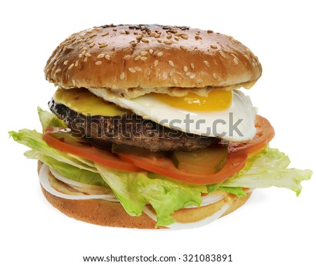 A delicious burger with cutlet, eggs, tomatoes, lettuce, onions, pickles
