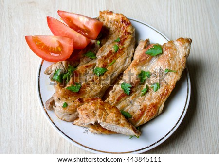 A delicious cooked pork steak garnished with parsley , fresh tomatoes sliced - stock photo
