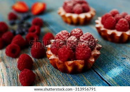 A delicious dessert for the whole family and easy diet, raspberry basket of unleavened dough with a gentle sprinkle with powdered sugar, fresh raspberries are a number of remaining dessert - stock photo