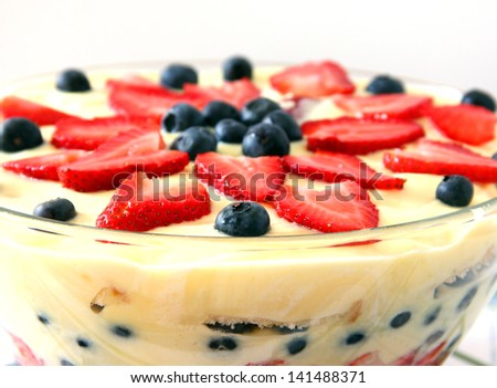 A delicious dessert with layers of cake and vanilla pudding topped with strawberries and blueberries.