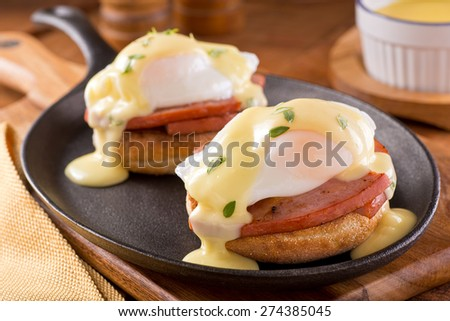 A delicious eggs benedict with thick cut ham, hollandaise sauce, and thyme garnish. - stock photo
