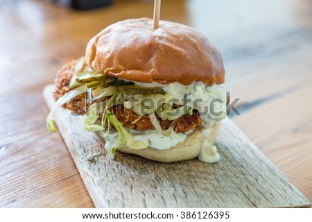 A delicious fried fish sandwich with lettuce, pickles and tartar sauce on a wood board