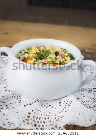 A delicious gluten free black bean, corn and quinoa salad in a white antique bowl.  The view is from the side.  - stock photo