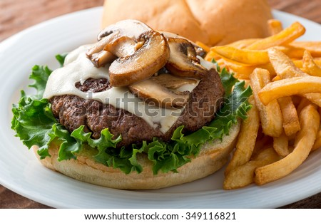 A delicious hamburger topped with swiss cheese and fried mushrooms on a kaiser. - stock photo