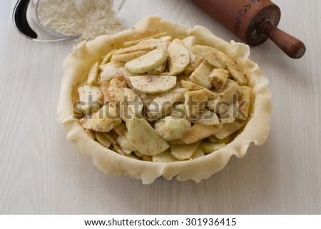 A delicious, handmade apple pie ready for the top and to be baked. Its mouth-watering apples and crust look good enough to eat even before baking. Lovely for anything related to baking, desserts, etc. - stock photo