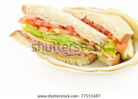 A delicious healthy ham, cheese and bologna sandwich, cut in half on a plate, white copy space - stock photo