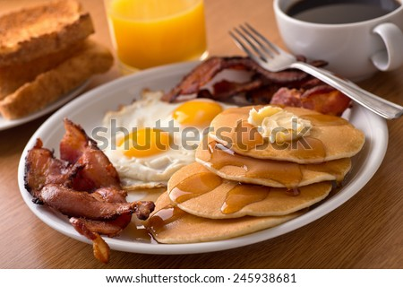 A delicious home style breakfast with crispy bacon, eggs, pancakes, toast, coffee, and orange juice. - stock photo