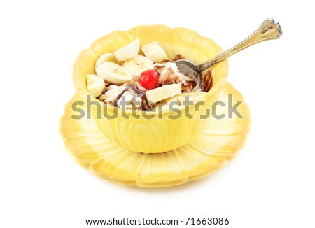 A delicious ice cream sundae with sliced bananas, hot fudge and a cherry in a yellow bowl, isolated on white