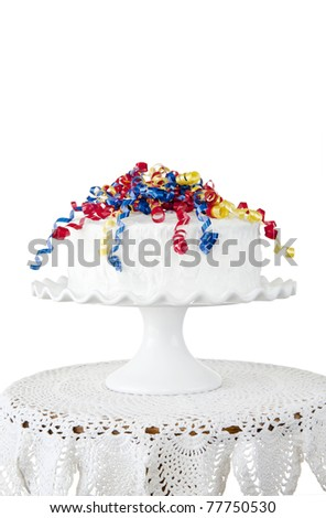 A delicious party cake with colorful ribbons on a cake stand with white background