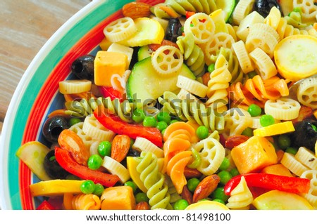 A delicious pasta salad on a picnic table - close overhead view - stock photo