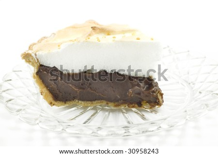 A delicious piece of homemade chocolate meringue pie on a plate isolated on white, vertical with copy space - stock photo
