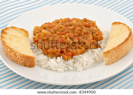 A delicious plate of lentils on white rice with toasted bread on the side.