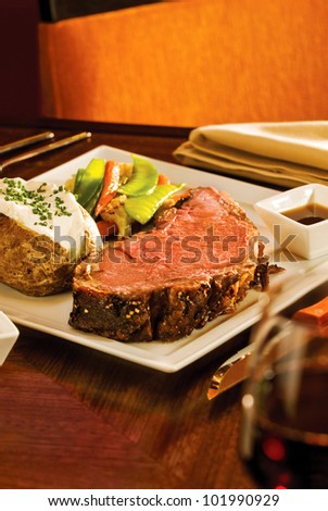 A delicious Prime Rib dinner with potato and extras. Narrow focus on the meat - stock photo