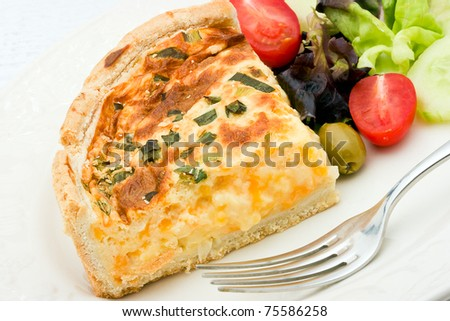 A delicious quiche with cheese and leeks on a white plate with salad of  mixed lettuce, tomatoes, olives and cucumber. - stock photo