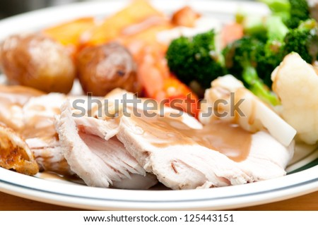 a delicious roasted turkey breast with gravy, vegetables and potatoes - stock photo