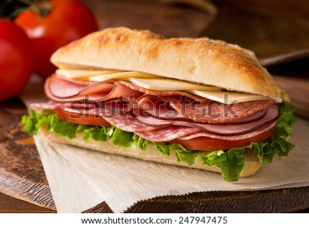 A delicious sandwich with cold cuts, lettuce, tomato, and cheese on fresh ciabatta bread. - stock photo