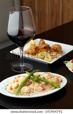 A delicious shrimp scampi pasta dish with red wine and friend shrimp appetizer in the background. - stock photo