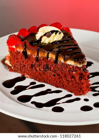 A Delicious Slice of Red Velvet Cake With Swirls and Streaks of Chocolate on a White Plate - stock photo