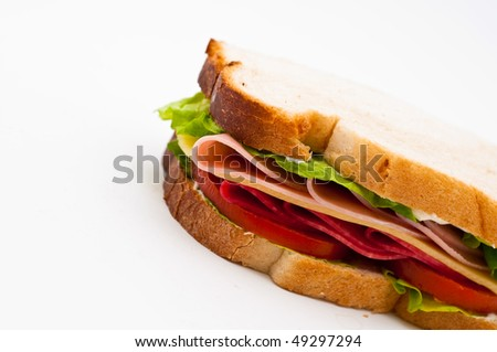 A delicious turkey and salami sandwich with cheese tomatoes lettuce isolated on a white background