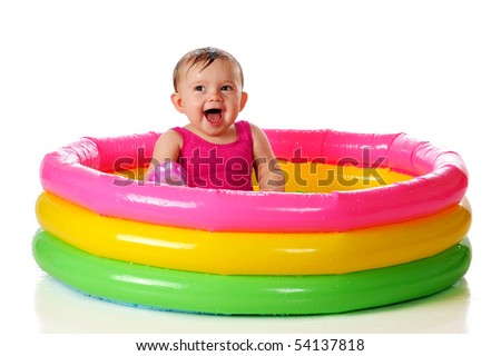 A delighted baby girl in a colorful kiddie pool.  Isolated on white. - stock photo
