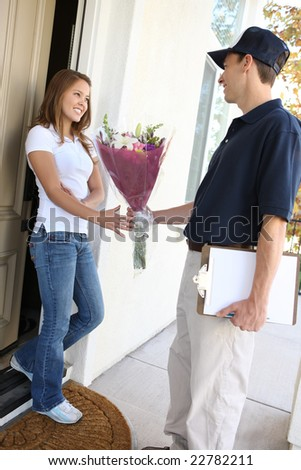 A delivery man giving flowers to pretty woman at home - stock photo