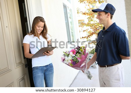 A  delivery man giving flowers to pretty woman at home