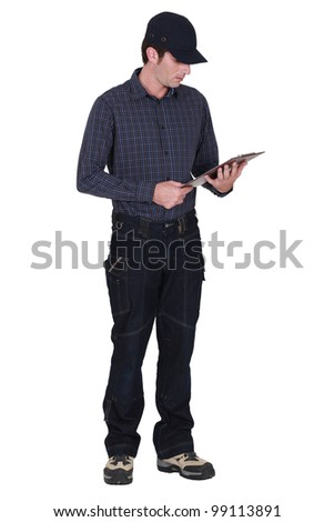 A delivery man looking down at his clipboard