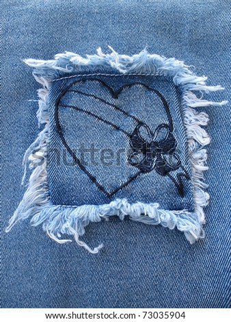 A denim square patch containing a heart with a blank banner across it. - stock photo
