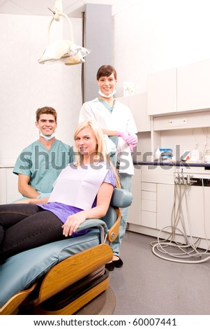 A dental clinic with dentist, assistant and patient - stock photo
