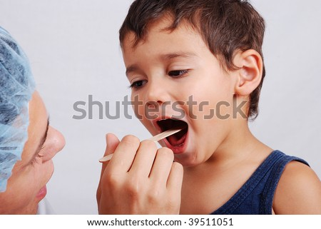 A dentist and cute kid with opened mouth - stock photo