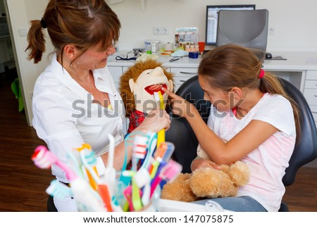 A dentistry doctor plays with a young girl Healthy teeth patient at dentist office dental caries prevention - stock photo